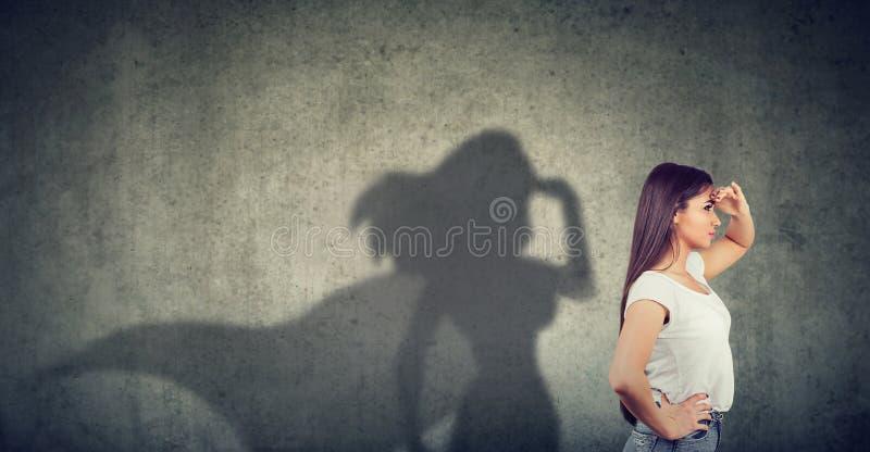 Opinião lateral uma mulher que imagina para ser um super-herói que olha aspirado fotografia de stock