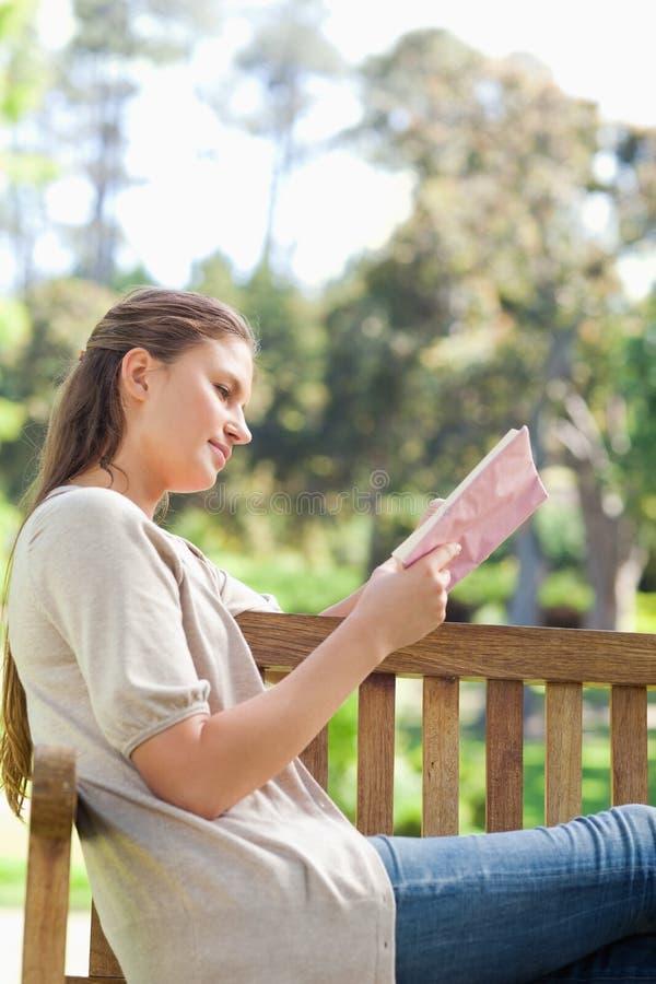 Opinião lateral uma mulher que lê um livro em um banco de parque imagens de stock