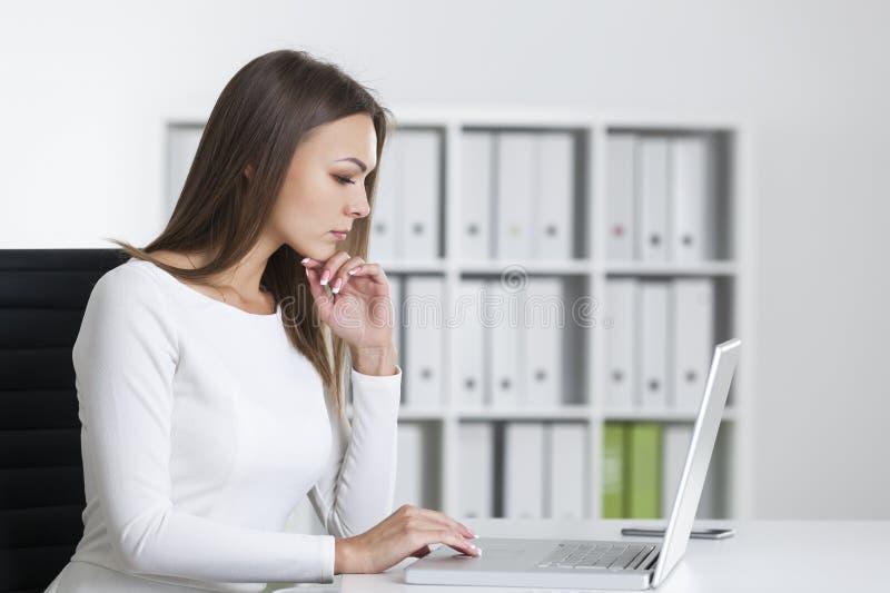 Opinião lateral uma mulher séria no portátil imagem de stock