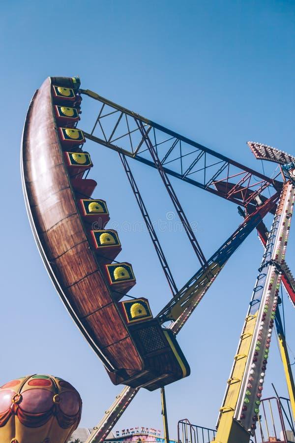Opinião lateral Viking Funfair Ride no parque de diversões sob o céu azul claro foto de stock