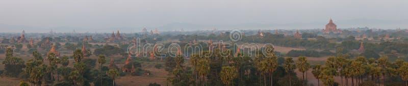 Opinião místico alaranjada da paisagem do nascer do sol com as silhuetas de templos antigos e de palmeiras velhos na névoa do alv imagem de stock