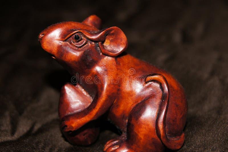 Opinião macro um rato marrom lustrado cinzelado de madeira bonito em um material escuro fotos de stock