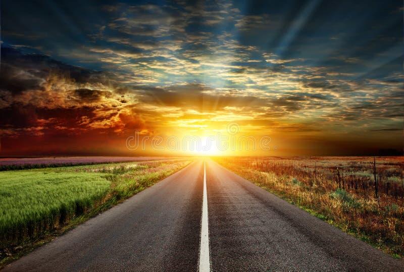 Opinião magnífica da estrada da estrada asfaltada no fundo do por do sol fotografia de stock