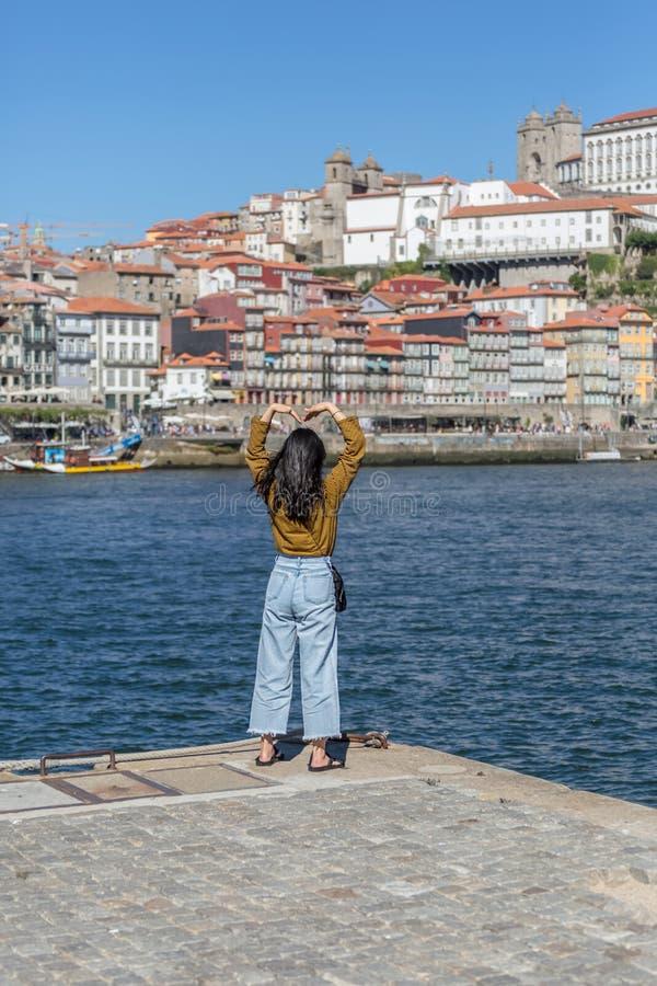 Opinião a menina da parte traseira que faz o coração com braços, rio de Douro e cidade de Porto como o fundo fotos de stock