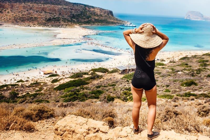 opinião a mulher bonita que veste um roupa de banho da parte na ilha que olha o mar e a praia, retrato da mulher atrativa no tróp fotos de stock