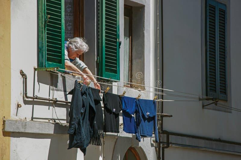 Opinião a mulher idosa que põe a roupa para secar na janela no ` Elsa de Colle di Val d foto de stock royalty free