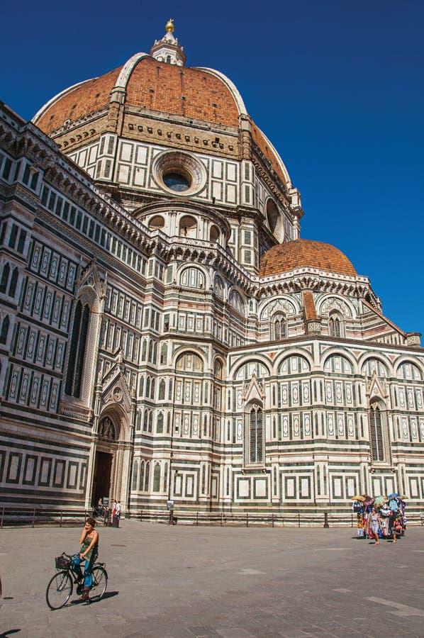 Opinião a mulher na bicicleta ao lado da catedral Santa Maria del Fiore em Florença fotos de stock royalty free