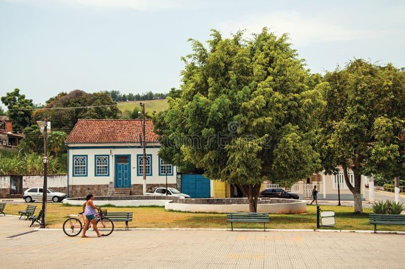 Opinião a mulher que anda com a bicicleta no quadrado de Bananal fotografia de stock royalty free