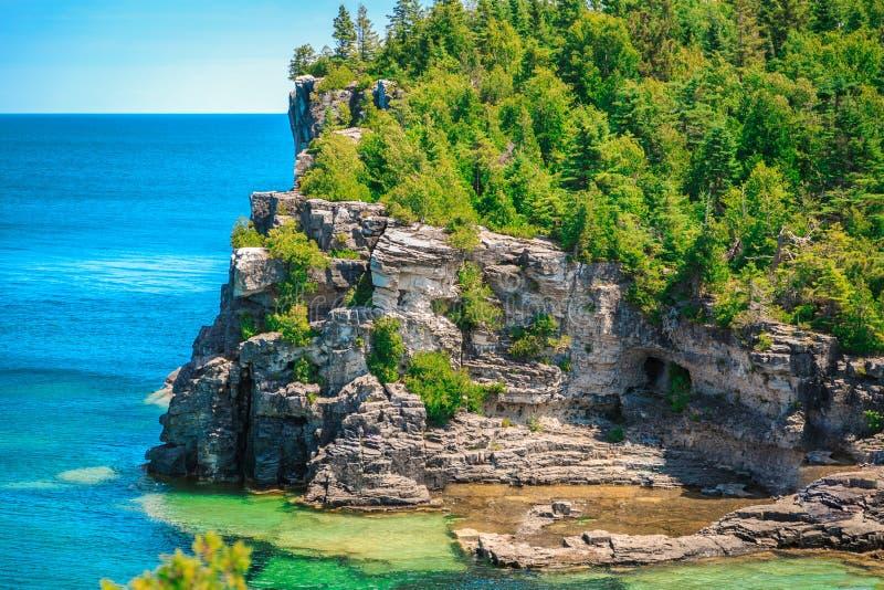 A opinião natural surpreendente da paisagem da praia rochosa e os azuis celestes tranquilos cancelam a água em Bruce Peninsula bo imagens de stock