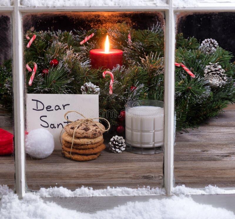 Opinião nevado da janela das cookies e do leite mais o cartão para Santa Claus fotografia de stock royalty free