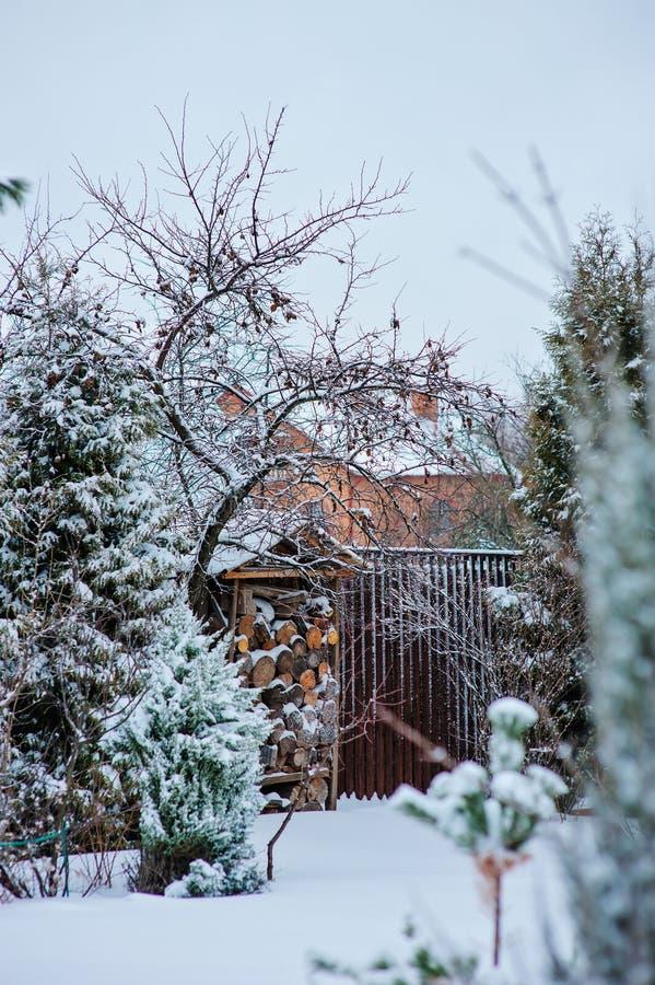 Opinião nevado do jardim do inverno com vertente e cerca da madeira foto de stock