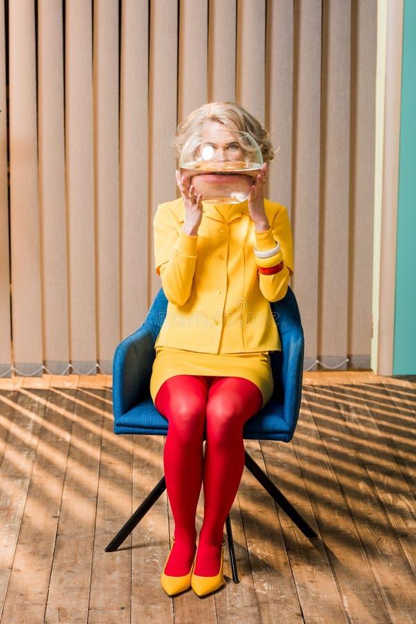 opinião obscurecida a mulher na roupa retro que guarda peixes dourados no aquário na boneca colorida do apartamento fotos de stock
