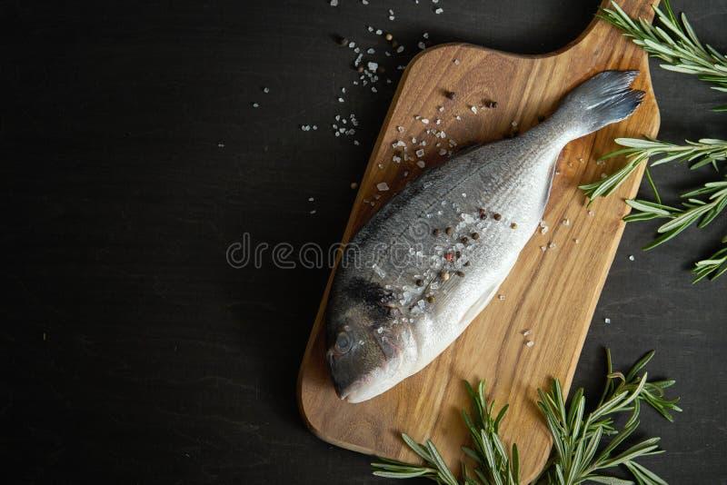 Opinião Op peixes crus frescos do dorada com alecrins, pimenta e sal em uma placa de madeira e em uma tabela preta imagem de stock royalty free