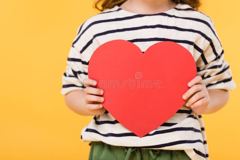 opinião parcial a criança com coração de papel vermelho nas mãos imagem de stock royalty free
