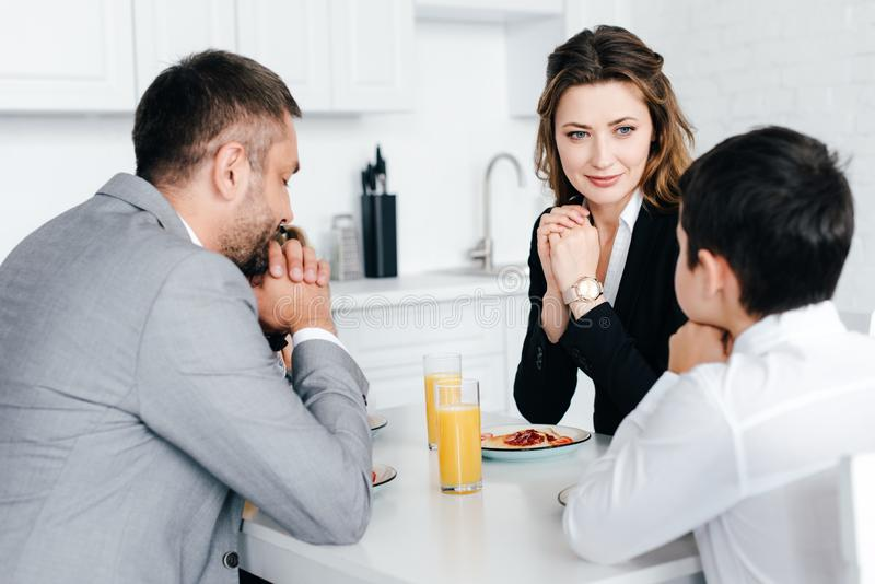 opinião parcial a família que reza junto durante o café da manhã imagens de stock royalty free