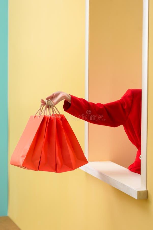 a opinião parcial a mulher à moda na roupa vermelha com os sacos de compras vermelhos que outstretching distribui a janela decora foto de stock royalty free