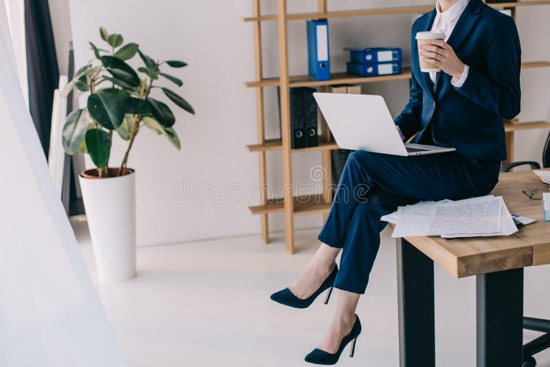 opinião parcial a mulher de negócios com o portátil e o café para ir sentar-se na tabela fotografia de stock