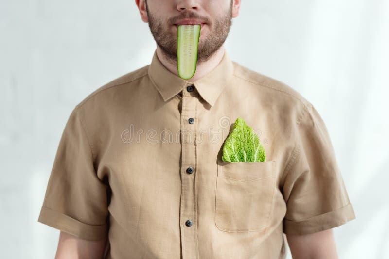 opinião parcial o homem com fatia do pepino na folha da boca e do couve-de-milão no estilo de vida do vegetariano do bolso fotografia de stock
