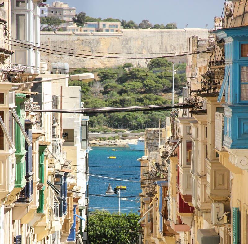 Opinião reta da rua com os balcões coloridos de Sliema a Manoel Island fotografia de stock