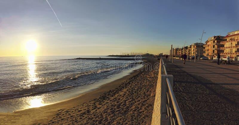 Opinião romana da rua da costa em Ostia Lido no tempo do por do sol com os povos que andam e para apreciar o dia de inverno bonit imagem de stock royalty free