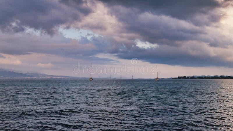 Opinião sombrio do céu e da água a Rio Antirio Bridge, Grécia fotografia de stock