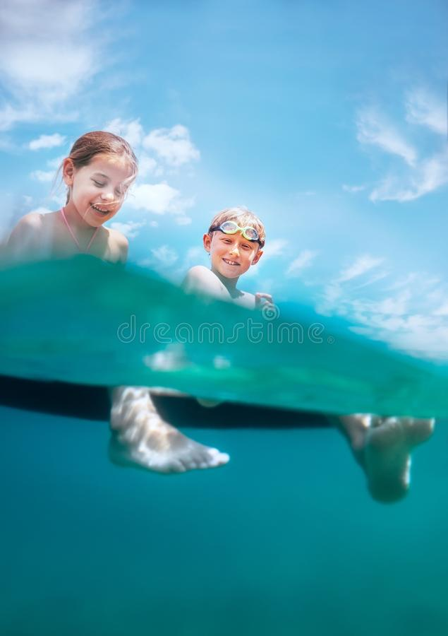 Opinião subaquática da câmera em duas crianças de sorriso felizes que sentam-se sobre imagem de stock