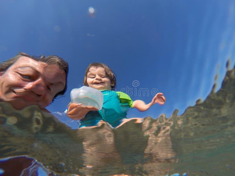 Opinião subaquática um pai e sua filha com as caras distorcidas que têm o divertimento no mar fotografia de stock