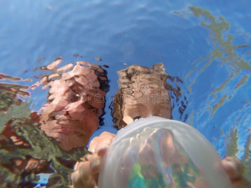 Opinião subaquática um pai e sua filha com as caras distorcidas que têm o divertimento no mar imagem de stock royalty free
