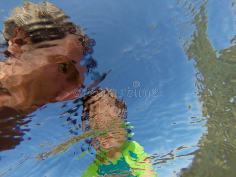 Opinião subaquática um pai e sua filha com as caras distorcidas que têm o divertimento no mar imagem de stock