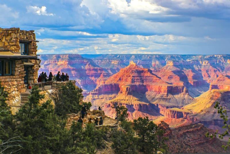 Opinião sul da borda de Grand Canyon na hora dourada sob o céu tormentoso com os turistas no ponto da vigia que toma imagens e se imagem de stock royalty free