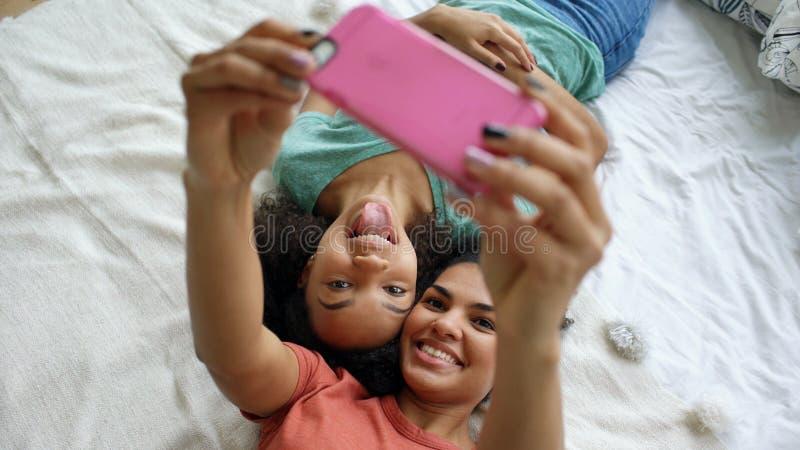 Opinião superior as amigas engraçadas bonitas da raça misturada que fazem o retrato do selfie na cama no quarto em casa imagens de stock