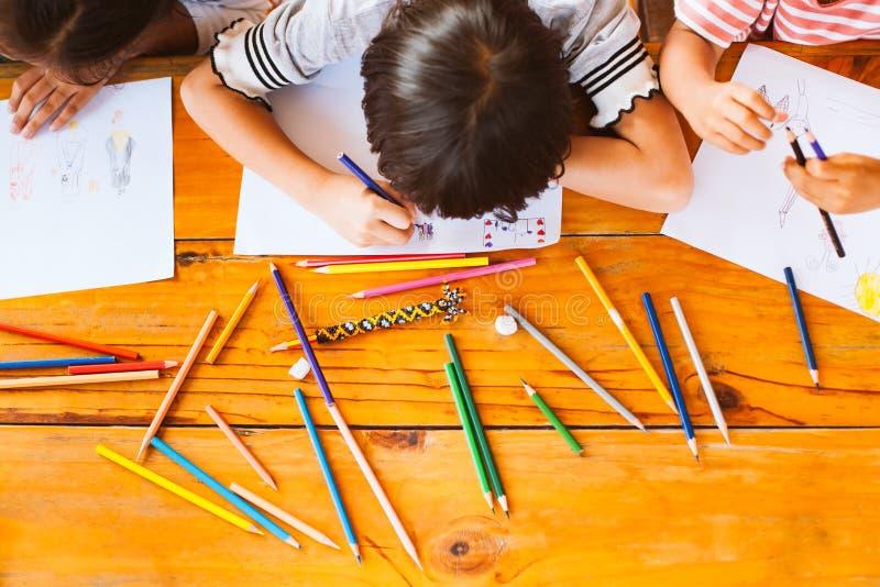 Opinião superior as crianças asiáticas do grupo que tiram e que pintam fotografia de stock