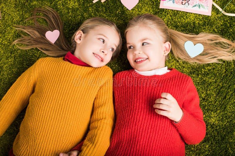 opinião superior as irmãs mais nova adoráveis que encontram-se no tapete cercado foto de stock