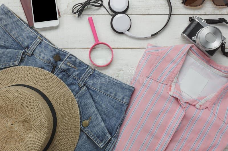 Opinião superior as mulheres da roupa dos acessórios a viajar com conceito do fundo da tecnologia fotos de stock