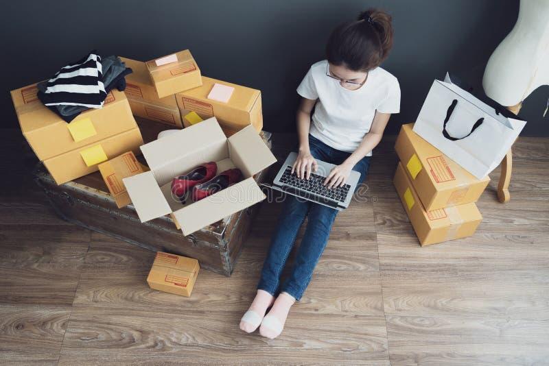 Opinião superior as mulheres que trabalham o laptop da casa no assoalho de madeira com pacote postal, vendendo o conceito em linh fotografia de stock
