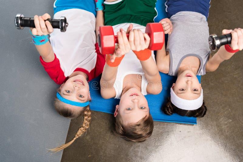 Opinião superior crianças bonitos no sportswear que encontra-se na esteira da ioga e que exercita com pesos no gym fotografia de stock royalty free
