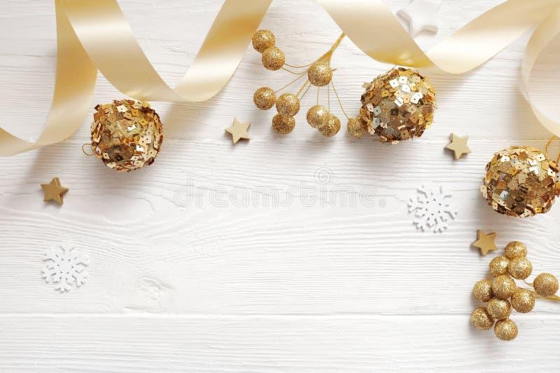 Opinião superior da decoração do Natal do modelo e bola do ouro, flatlay em um fundo de madeira branco com uma fita, com lugar pa foto de stock