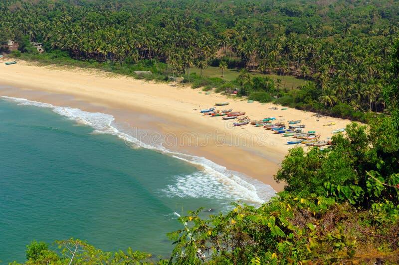 Opinião superior da perspectiva da praia amarela da areia com o mar tropico azul de um lado e das árvores verdes e das palmas do  fotos de stock royalty free