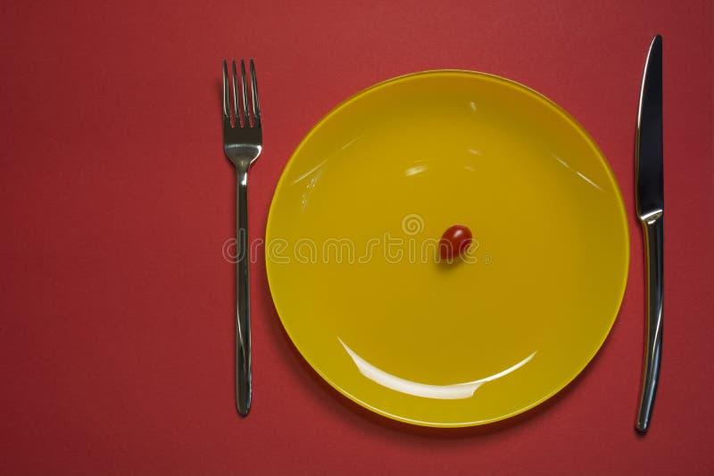 Opinião superior da placa do conceito da dieta Tomate de cereja na placa vazia amarela com forquilha e na faca no fundo vermelho foto de stock royalty free