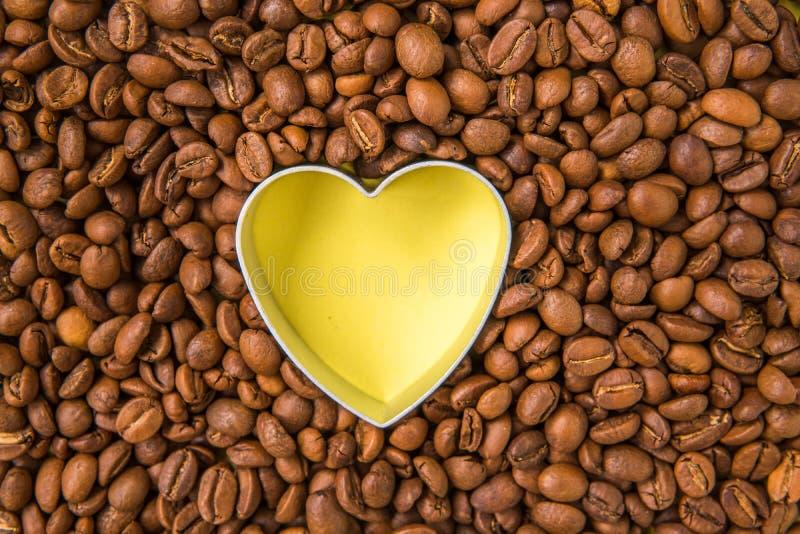 Opinião superior dada forma do coração dos feijões de café Coração amarelo entre o cof cru imagens de stock