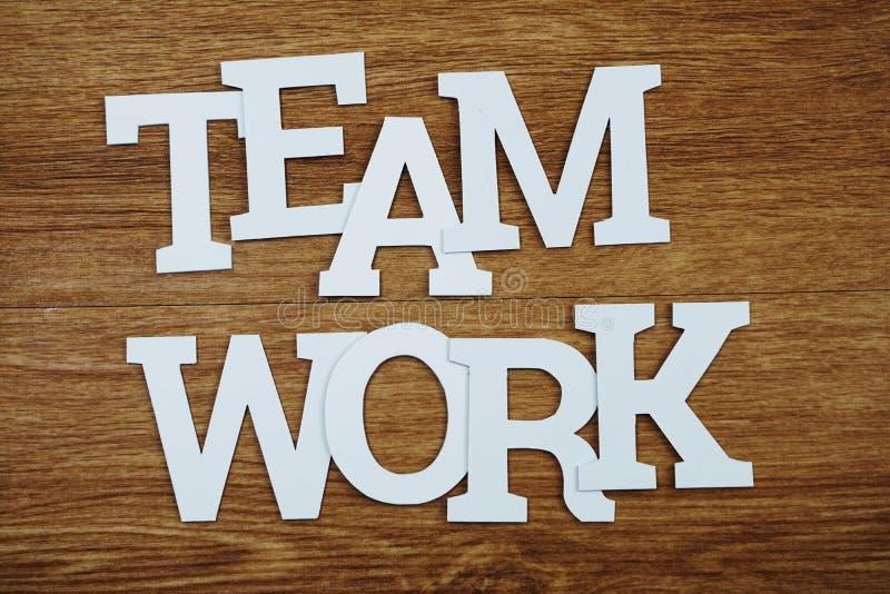 Opinião superior do alfabeto das letras do texto dos trabalhos de equipe no fundo de madeira imagens de stock royalty free