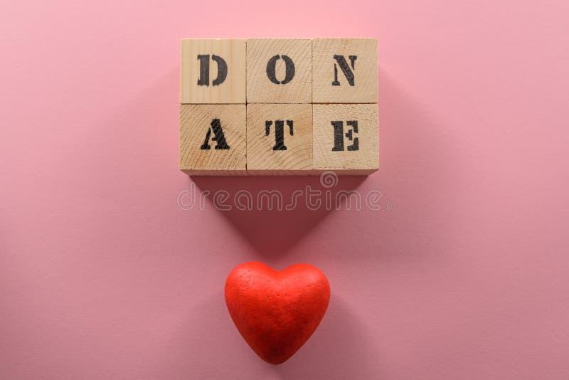 A opinião superior do close-up de cubos de madeira com palavra doa e símbolo vermelho do coração imagem de stock