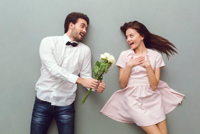 Opinião superior dos pares novos no ramalhete cinzento das rosas do fundo fotografia de stock