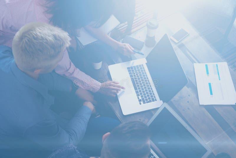 Opinião superior a equipe nova dos colegas de trabalho que fazem a grande discussão do trabalho no escritório moderno Homem que d imagens de stock royalty free