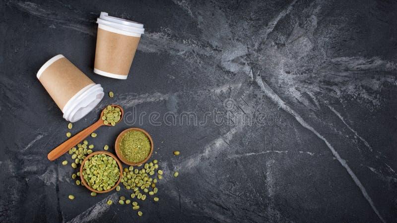 Opinião superior feijões de café à terra unroasted verdes crus em umas bacias e na colher de madeira com os copos para viagem des imagens de stock royalty free
