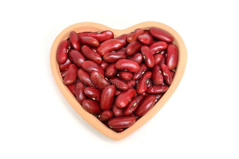 Opinião superior feijões vermelhos no coração de madeira isolado no backgrou branco fotos de stock royalty free
