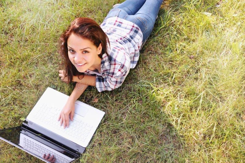 Opinião superior a menina do estudante que trabalha no portátil, encontrando-se na grama no parque imagem de stock royalty free