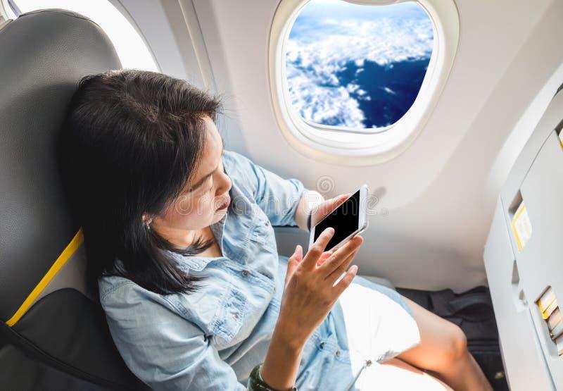 Opinião superior a mulher asiática que senta-se no assento de janela no avião e no t fotos de stock