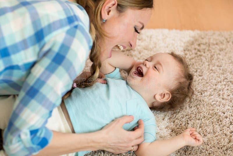 Opinião superior a mulher bonita e seu o filho do bebê da criança que sorriem ao encontrar-se no assoalho fotos de stock