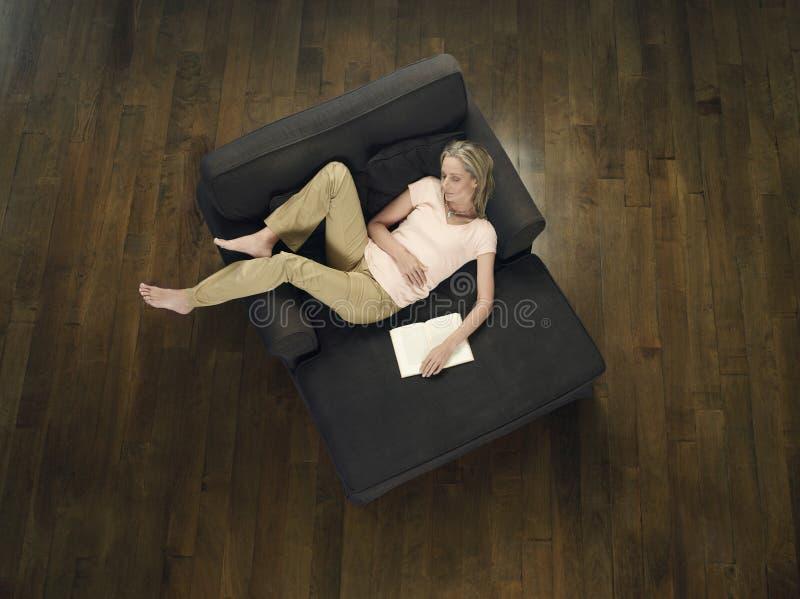 Opinião superior a mulher com livro que dorme no sofá imagem de stock